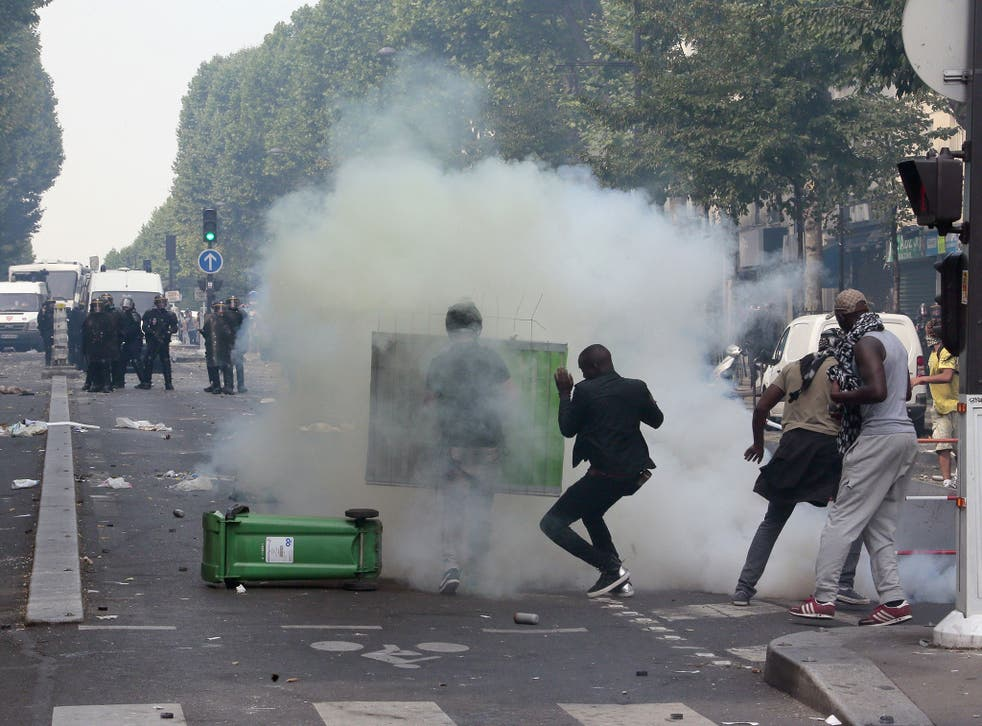Protesters clash with riot police near the Barbes-Rochechouart aerial metro station