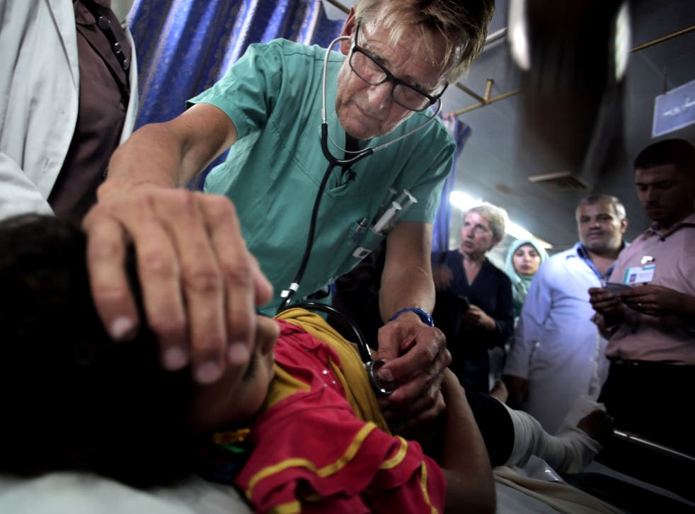Mads Gilbert, a Norwegian doctor who is volunteering at Shifa, treats a Palestinian girl at the emergency room