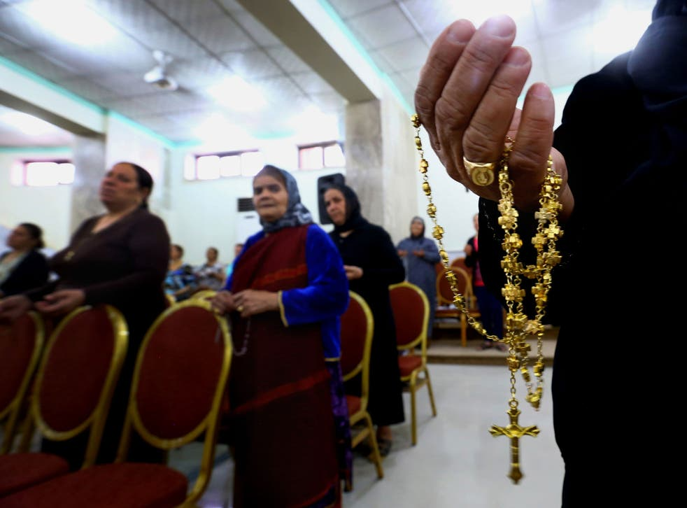 Displaced Christians who fled the violence in Mosul pray at Mar Aframa church in Qaraqoush on the outskirts of the city. Many have been stripped of their possessions