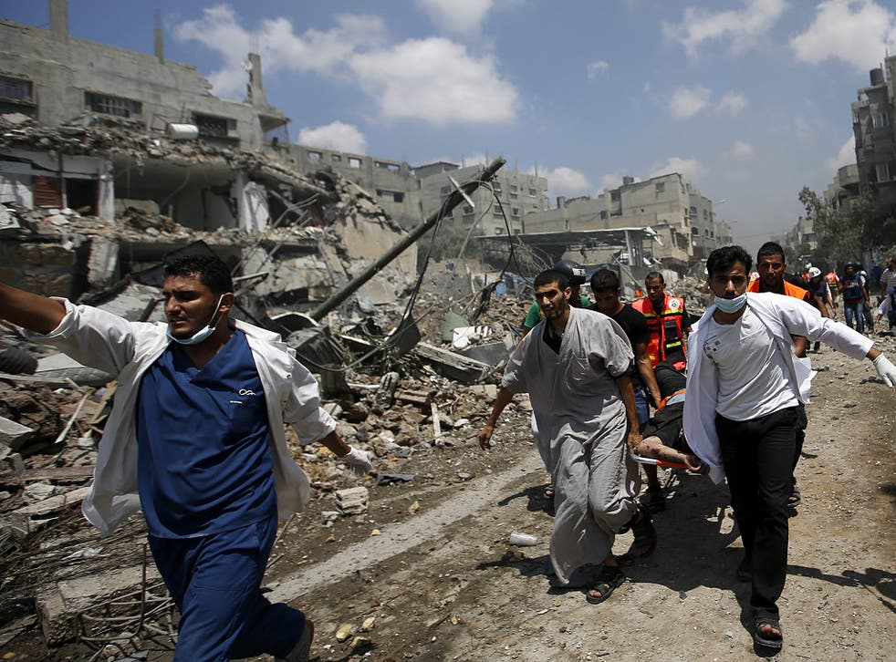 Palestinians paramedics lift the body of a man from the Al Shejaeiya neighbourhood, during a brief period of ceasefire requested by local rescue forces to retrieve dead and wounded from the Shuja'iyya neighbourhood in east Gaza City