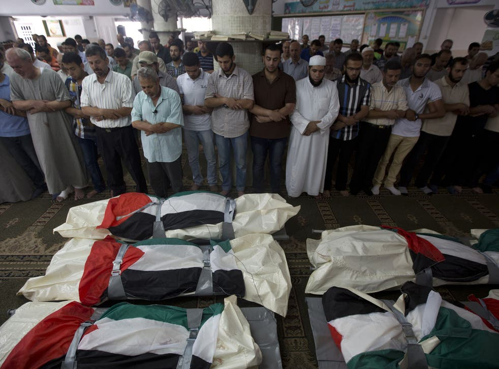 Palestinian mourners pray over five bodies, all from the Halaq family, during their funeral in the Jabalia refugee camp, in the Gaza Strip, on 21 July 2014