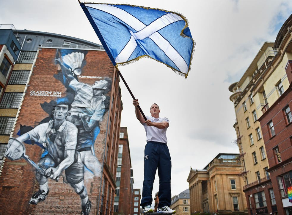 Euan Burton, multiple World and European medal winning judoka poses with the Scottish Saltire flag