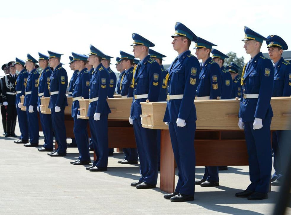 Four coffins with the remains of a victim of the Malaysia Airlines flight MH17 are carried to a military plane during a ceremony on the airport of Kharkiv, Ukraine, 23 July 2014.