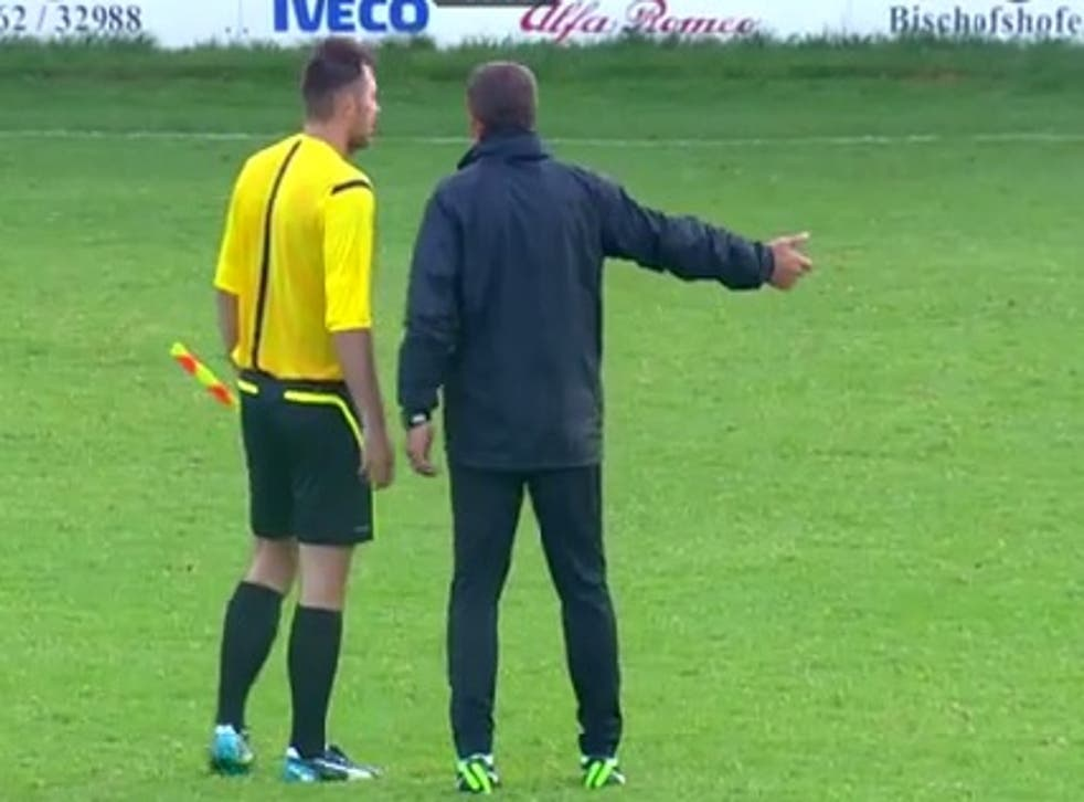 A member of Maccabi Haifa's staff speaks to the referee as the match is abandoned