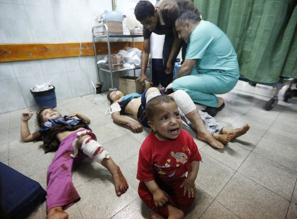 Palestinian children, wounded in an Israeli strike on a compound housing a U.N. school in Beit Hanoun, in the northern Gaza Strip, cry as they lay on the floor at the emergency room of the Kamal Adwan hospital in Beit Lahiya