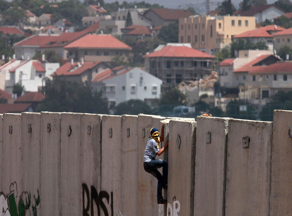 A Palestinian protester climbs Israel's controversial separation barrier during clashes with Israeli security forces following a demonstration against Israeli settlements