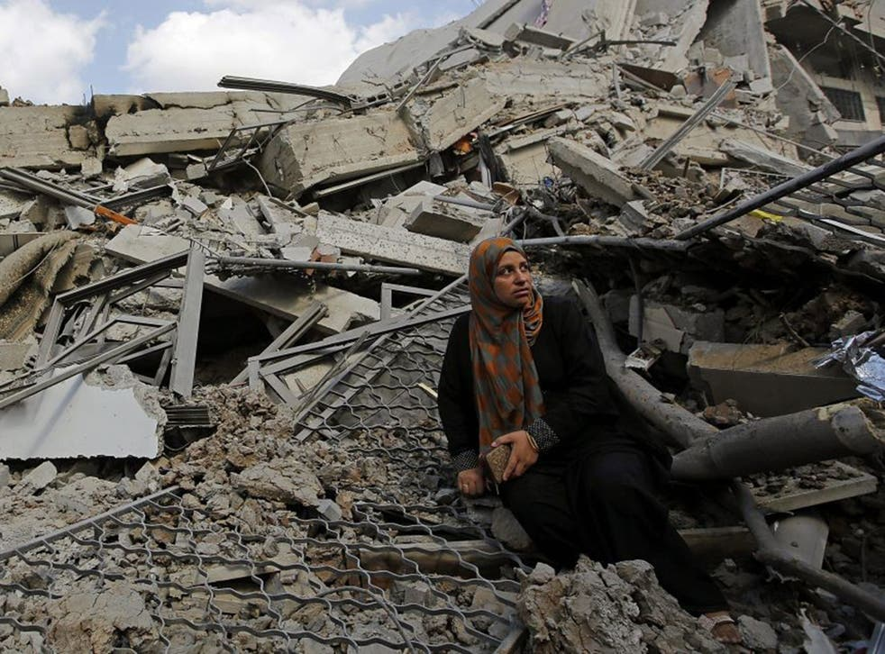 A Palestinian woman sits at the ruble of her destroyed house in Shuja'iyya neighbourhood in eastern Gaza City