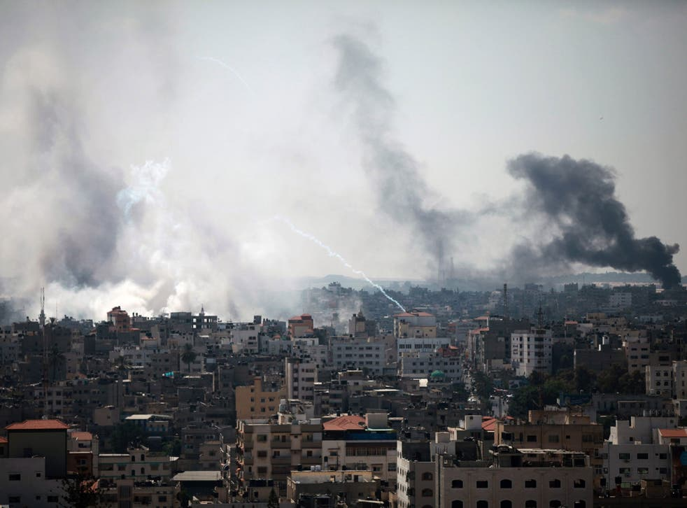 Smoke rises after Israeli tanks shell the Shujaiya neighbourhood during a military operation in the east of Gaza City, 27 July 2014