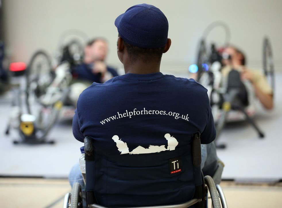 Amputee Corie Mapp watches as other wounded servicemen use some of the exercise machines in the new Help for Heroes' Tedworth House rehabilitation centre for wounded servicemen and women during a press preview day on October 18, 2012 in Tidworth, England.