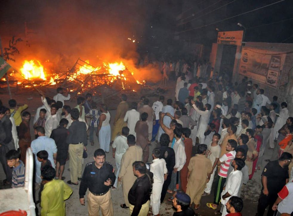 Police arrive after the houses of religious minority group Ahmadiyyas, were torched by a mob following accusations of blasphemy, in Gujranwala, Pakistan, 28 July 2014