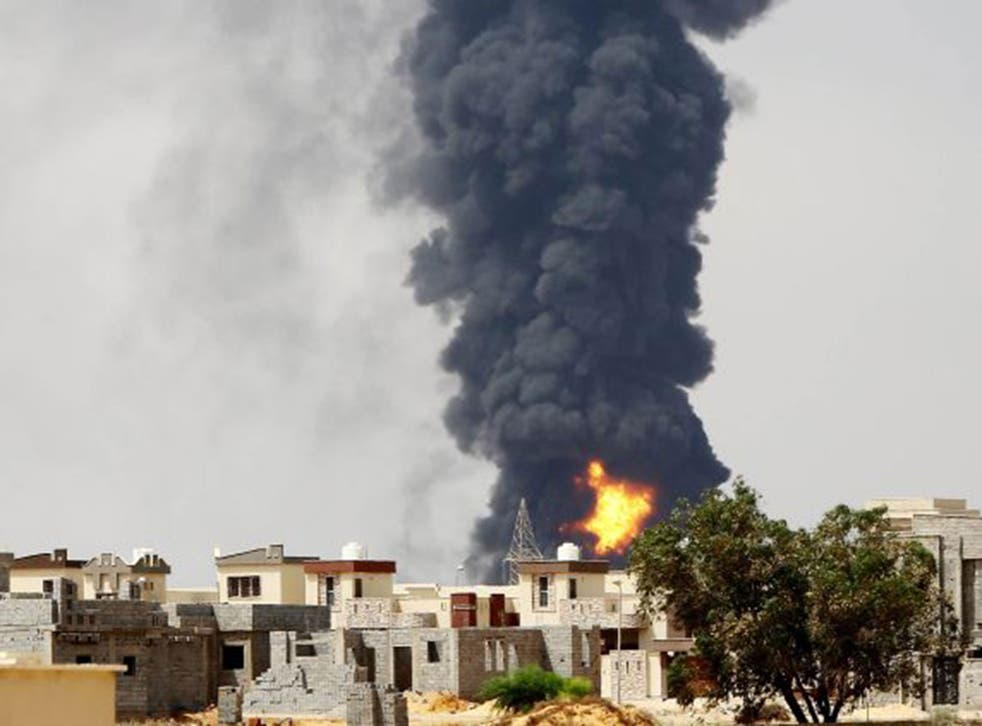Smoke billows from the oil depot following clashes near Tripoli airport