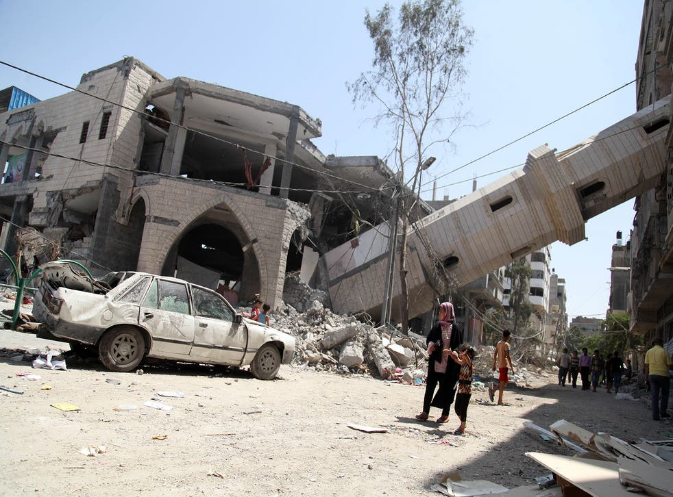 Palestinians walk past the collapsed minaret of a destroyed mosque in Gaza City, after it was hit in an overnight Israeli strike
