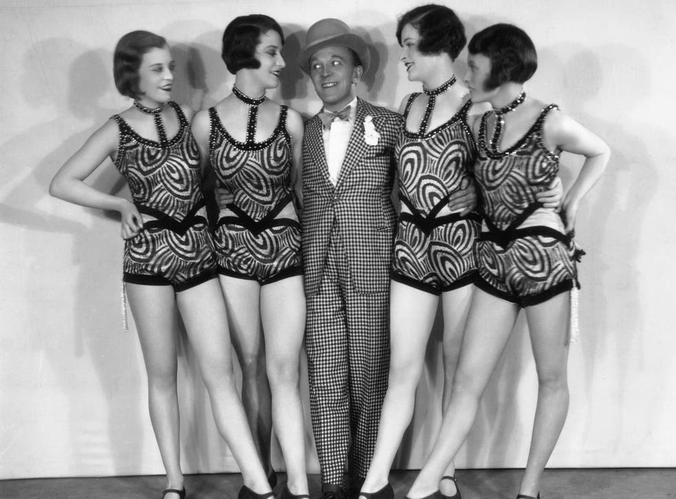 A suited man eyes up the moral calibre of a burlesque troupe