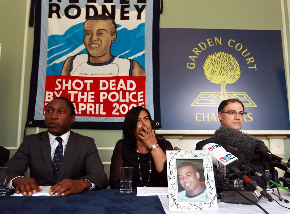 Susan Alexander sits behind a photograph of her son Azelle, at a press conference last year
