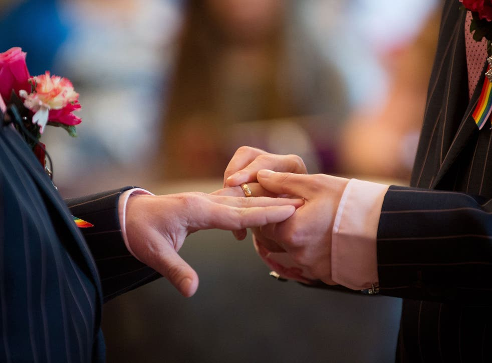 To grooms exchange rings during their wedding ceremony in Brighton