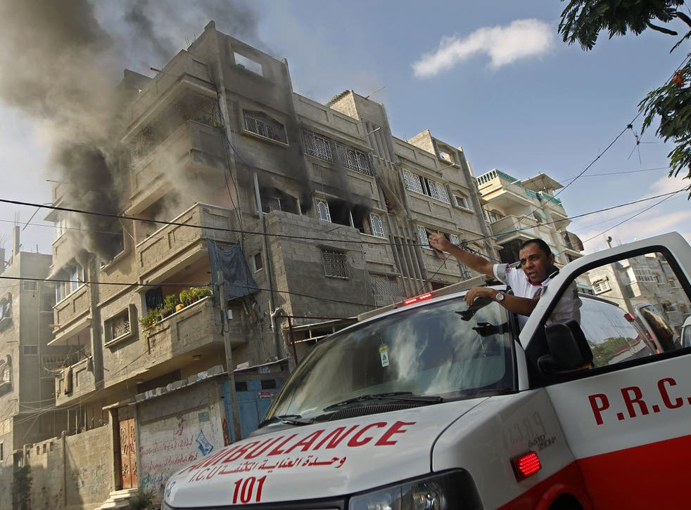 A Red Crescent ambulance driver points at a burning building in Rafah