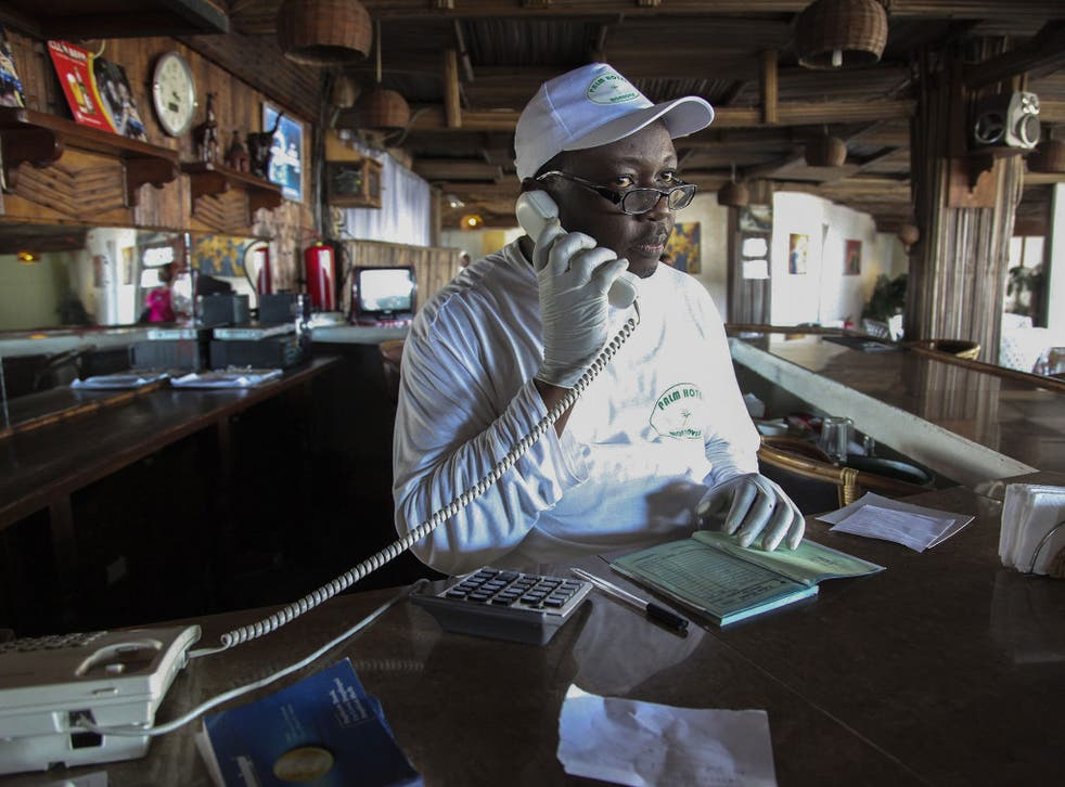 A Liberian receptionist wearing protective gloves to avoid the deadly Ebola virus works at a local hotel in Monrovia, Liberia