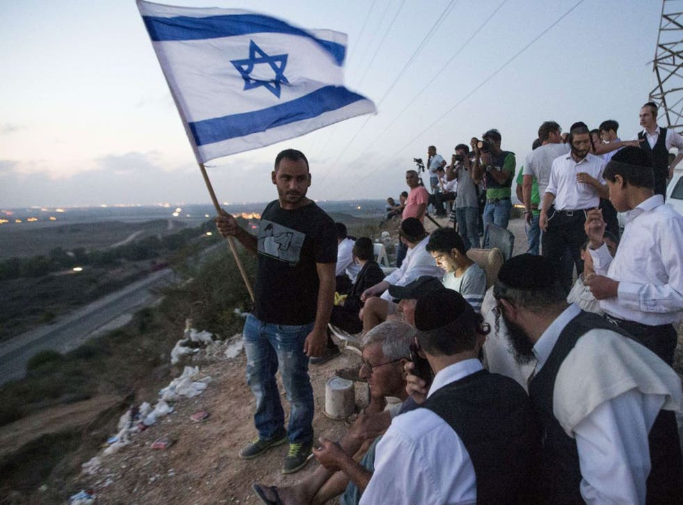 Top down: Israelis, on a hill overlooking Gaza, watch the fighting