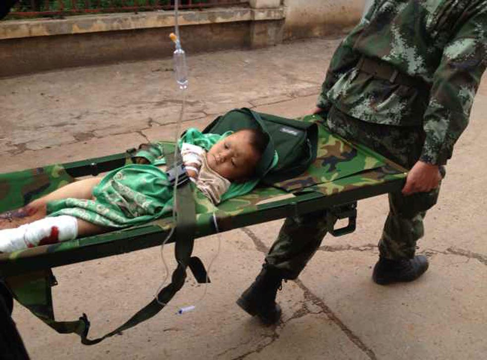 Rescuers carry an injuried child on a stretcher after a 6.1 magnitude earthquake hit the area in Ludian county