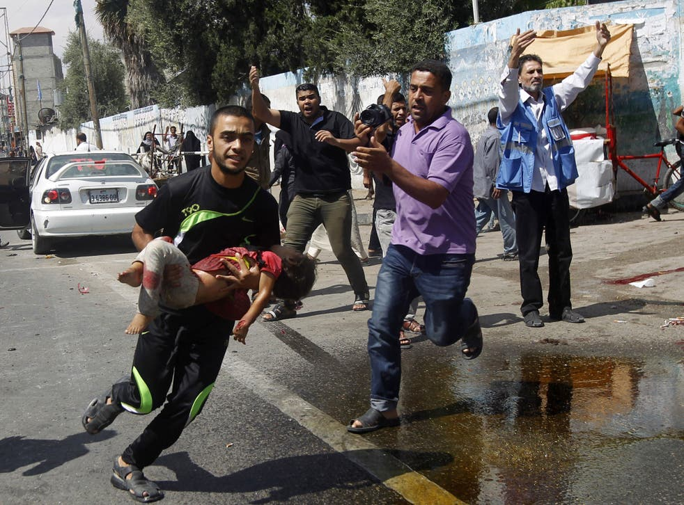 A Palestinian man carries an injured child following the Israeli military strike on the UN shelter in Rafah