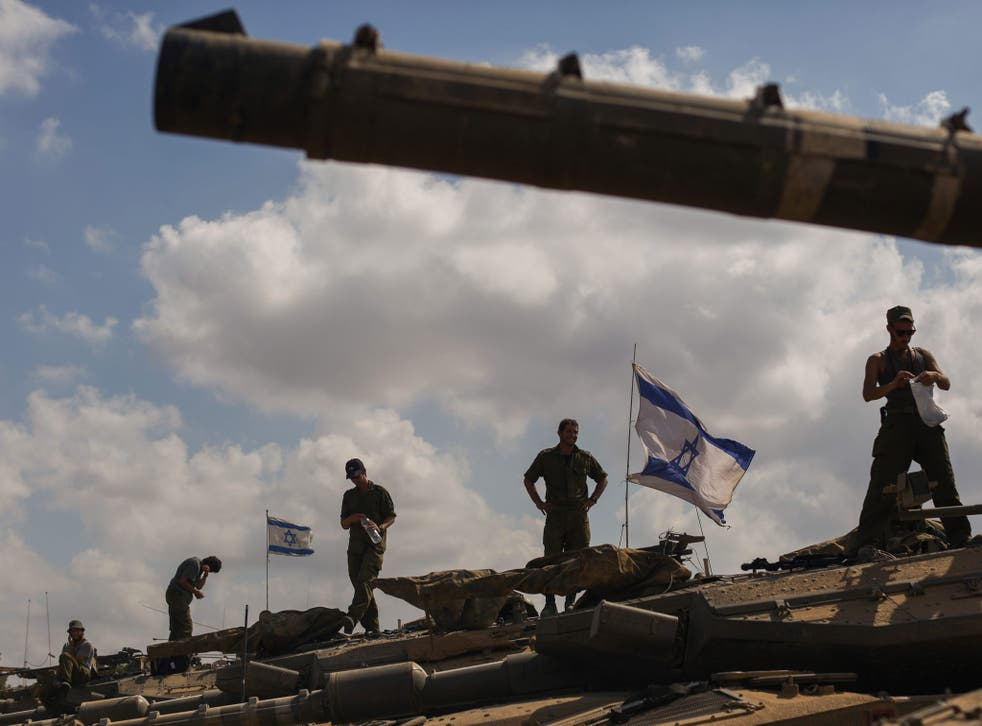 Troops stand on their tanks on the Israeli border after being withdrawn from the Gaza Strip but there has been no order to end the operation