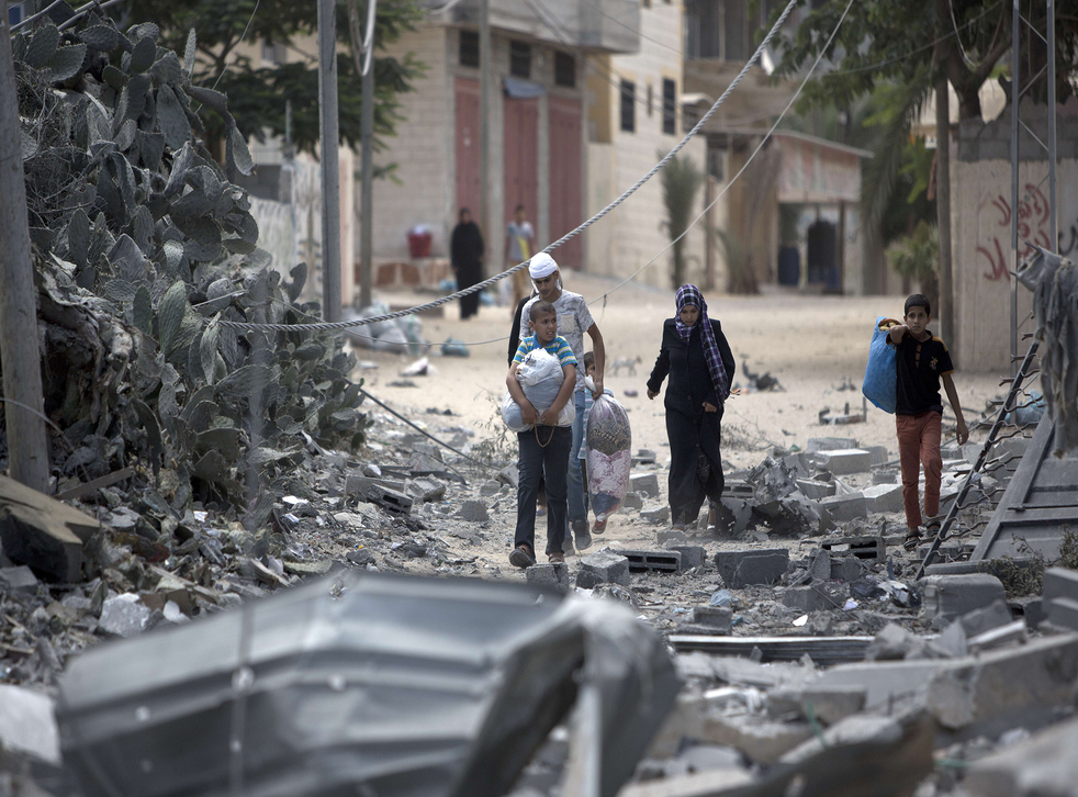 Palestinians carry bags as they return to check on what is left of their homes and businesses following the Israeli military offensive, close to the Rafah refugee camp, in southern Gaza Strip