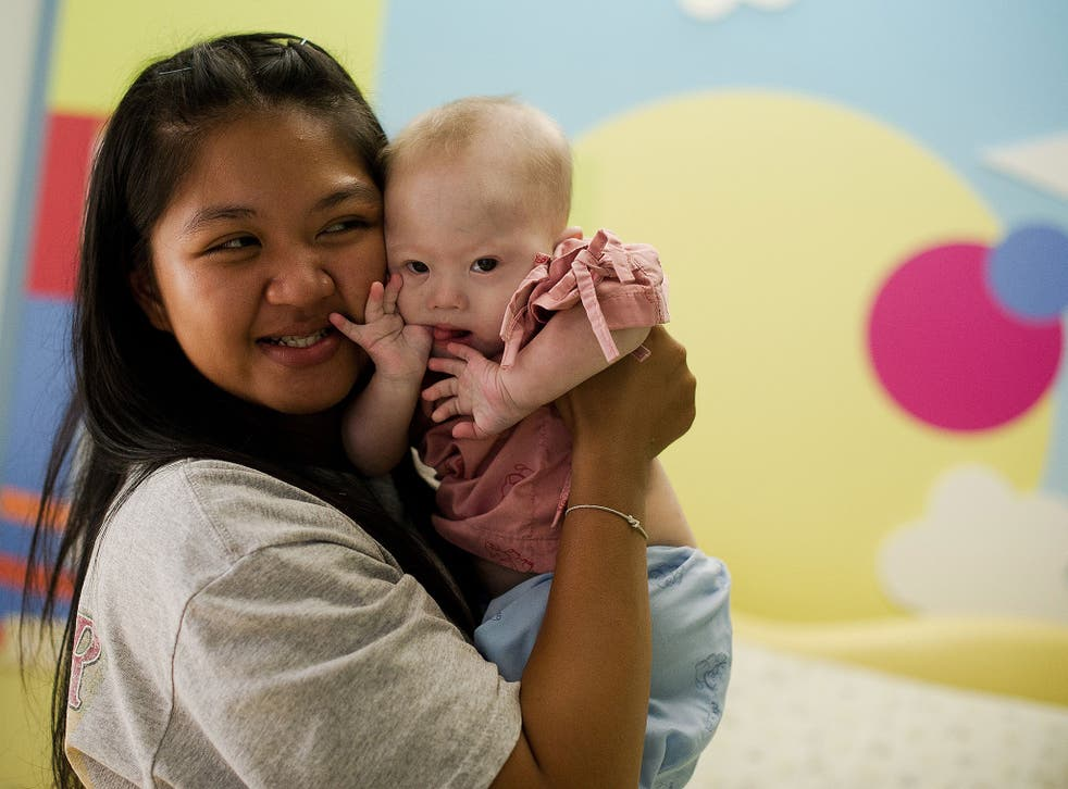 Thai surrogate mother Pattaramon Chanbua (L) holds her baby Gammy, born with Down Syndrome, at the Samitivej hospital, Sriracha district in Chonburi province on August 4, 2014. The surrogate mother of a baby reportedly abandoned by his Australian parents