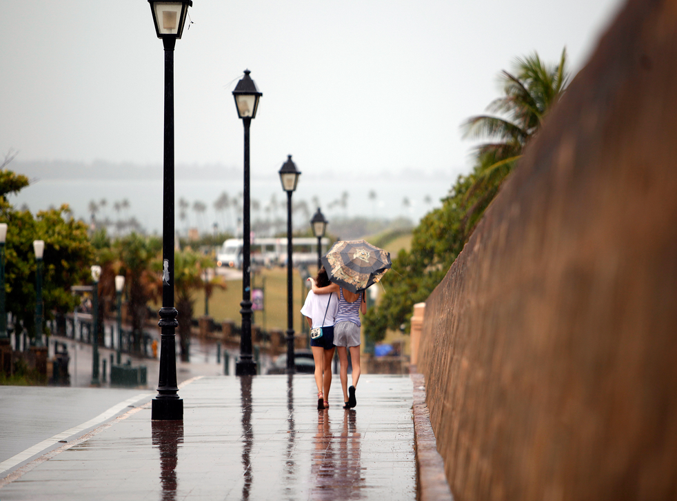 Two women walk with the protection of an umbrella in Old San Juan, Puerto Rico. Bertha pushed just south of Puerto Rico on Saturday as it unleashed heavy rains and strong winds across the region