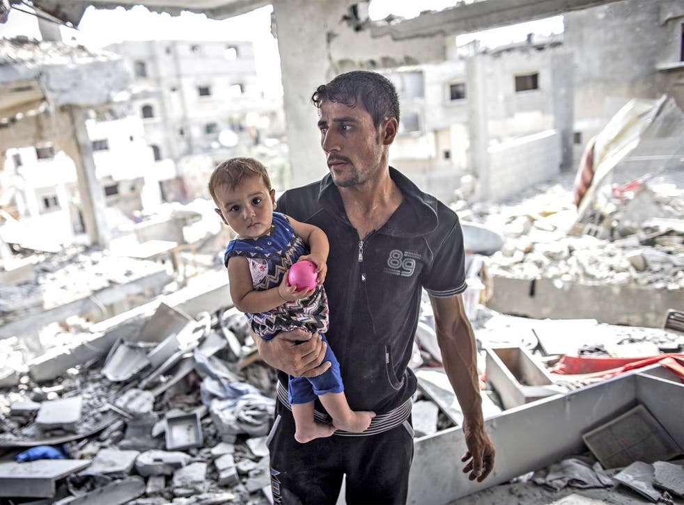 A Palestinian man holds his child in his destroyed home in Beit Hanoun