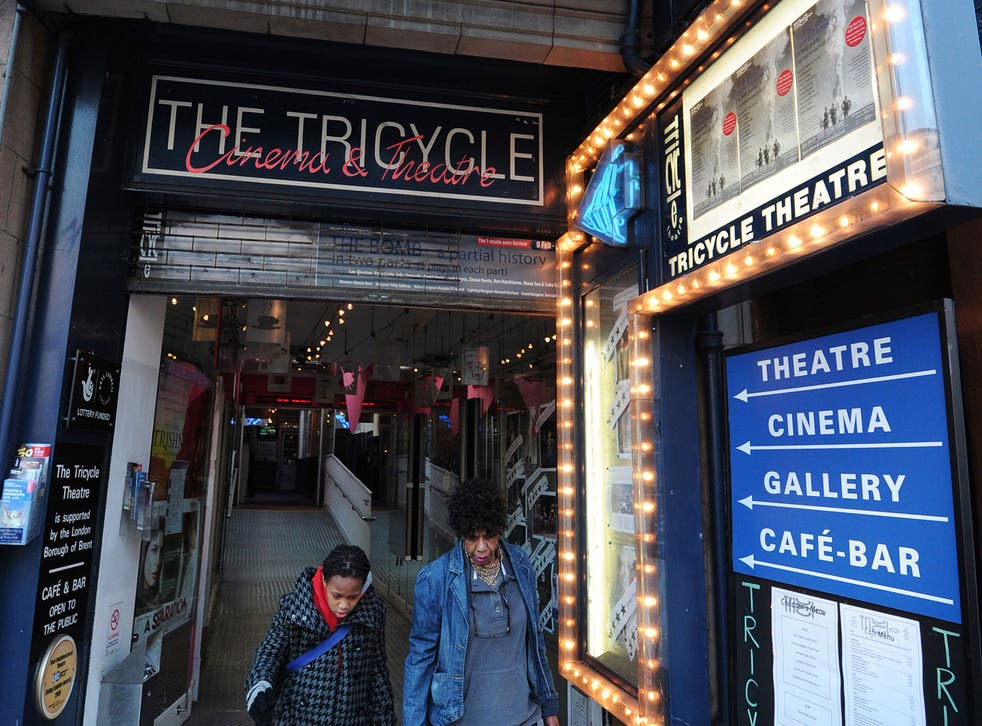 People walk through the entrance of the Tricycle Theatre in north London