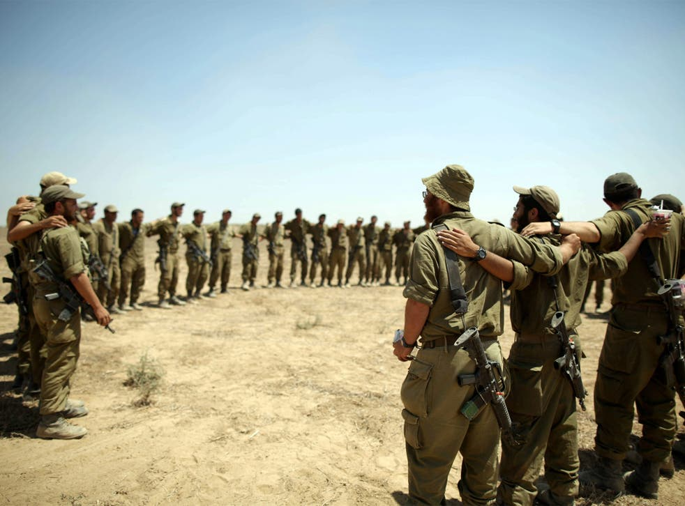Israeli soldiers embrace each other as they sing at a staging area at an unspecified location near the Gaza border