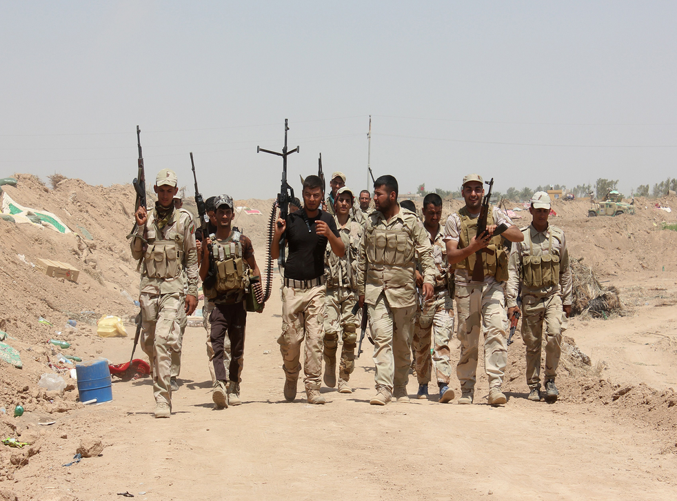 Iraqi volunteers who joined government forces to fight against Sunni jihadist militants of the Islamic State (IS) hold a position at a checkpoint in Udhaim