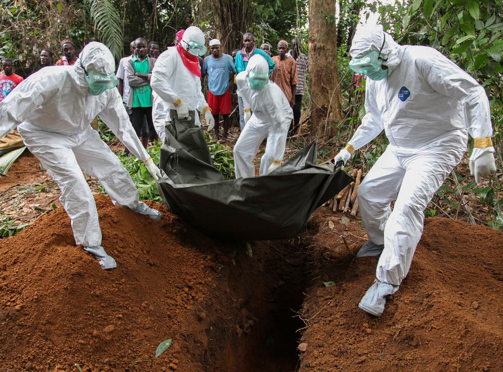 Liberian nurses in protective clothing bury the body of an Ebola victim in the Banjor community on the outskirts of Monrovia, a city in the grip of a real-life nightmare