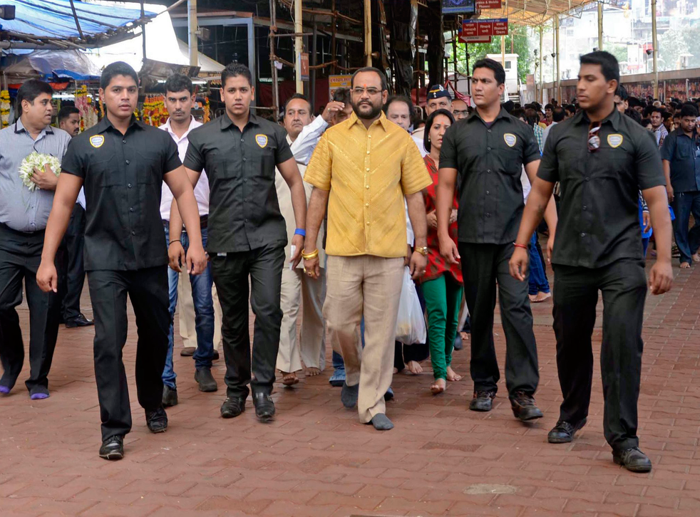 Indian businessman Pankaj Parakh is escorted as he is wearing a four-kilograms shirt made of gold in Mumbai, India.