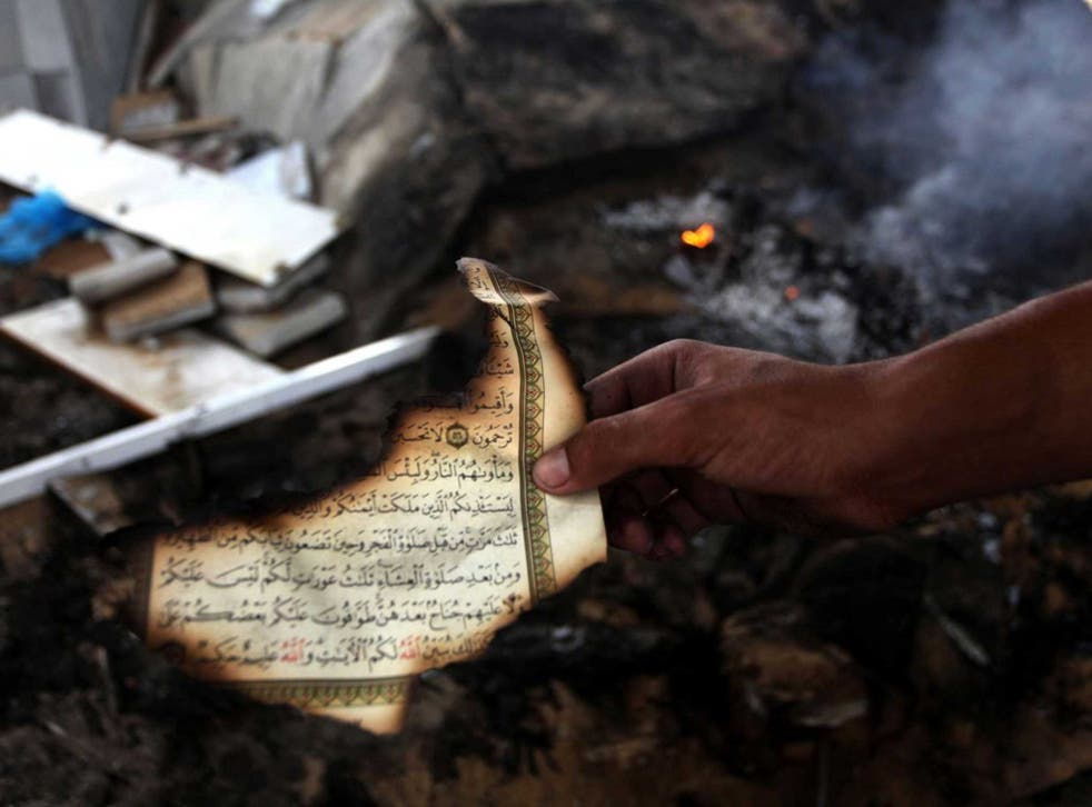 A man holds the remains of a Koran after another mosque was bombed in Gaza