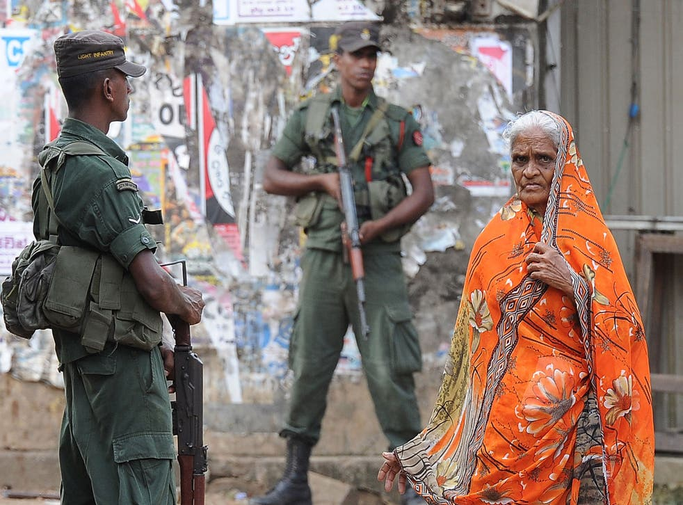 A Sri Lankan Muslim woman walks past soldiers following clashes between Muslims and an extremist Buddhist group in the town of Alutgama on June 17, 2014