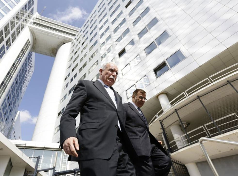 Palestinian Foreign Minister Riad al-Malki, left, leaves the International Criminal Court in The Hague, on August 5, 2014