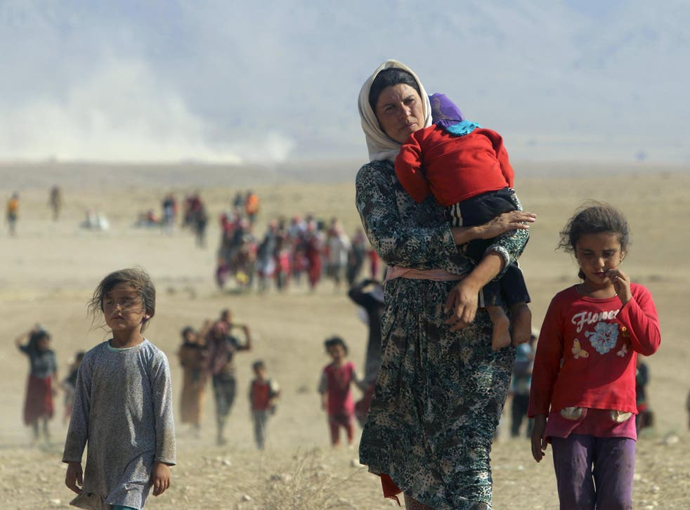 Displaced people from the minority Yazidi sect, fleeing violence from forces loyal to the Isis in Sinjar town, walk towards the Syrian border, on the outskirts of Sinjar mountain, near the Syrian border town of Elierbeh of Al-Hasakah Governorate