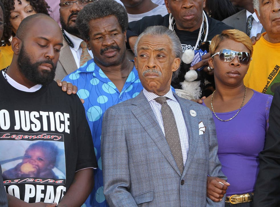 Michael Brown's parents, Michael Brown Sr., left, and Lesley McSpadden, right, stand next to the Rev Al Sharpton in St Louis on Tuesday