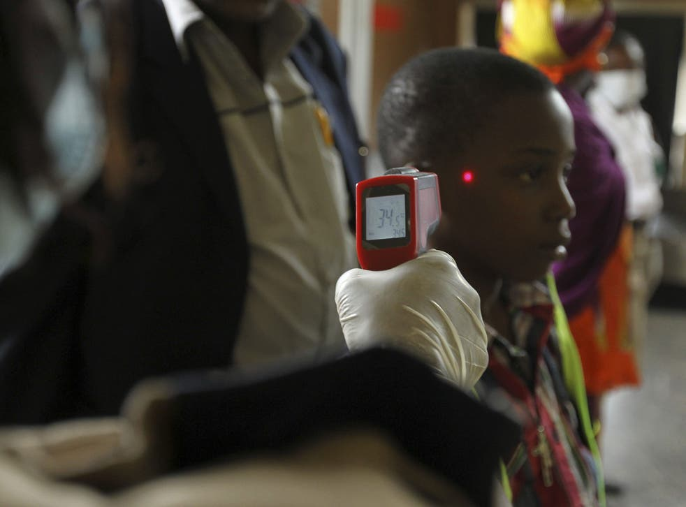 A boy's temperature is taken using an infrared laser thermometer at the international airport in Abuja, Nigeria