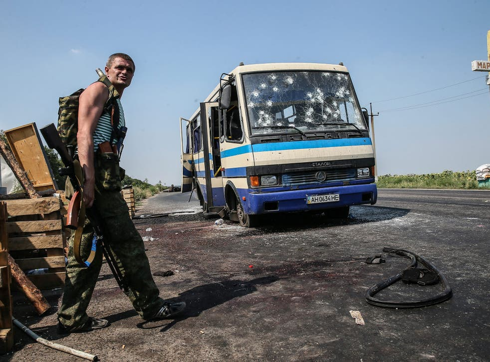 An armed pro-Russian separatist stands near the Ukrainian government-allied Right Sector's bus that was ambushed in Donetsk yesterday. At least 12 people were killed in the attack
