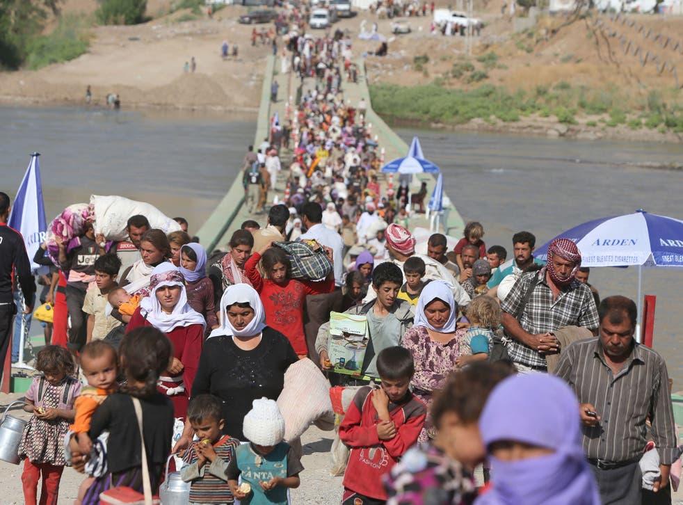 Displaced Iraqis from the Yazidi community cross the Syrian-Iraqi border along the Fishkhabur bridge over the Tigris River at the Fishkhabur crossing, in northern Iraq, on August 13, 2014.