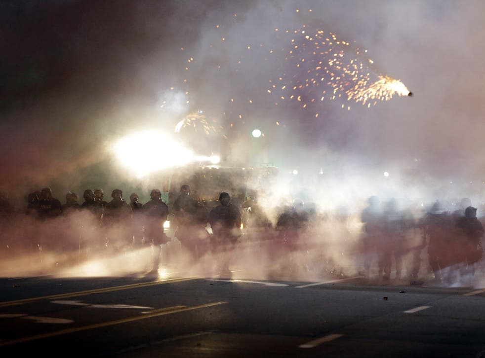 An explosive device deployed by police flies in the air as police and protesters clash Wednesday, Aug. 13, 2014, in Ferguson