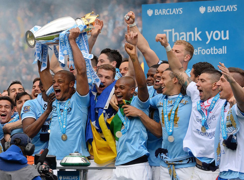 Manchester City's Belgian midfielder Vincent Kompany celebrates with the trophy after his team won the Premiership title on May 11, 2014.
