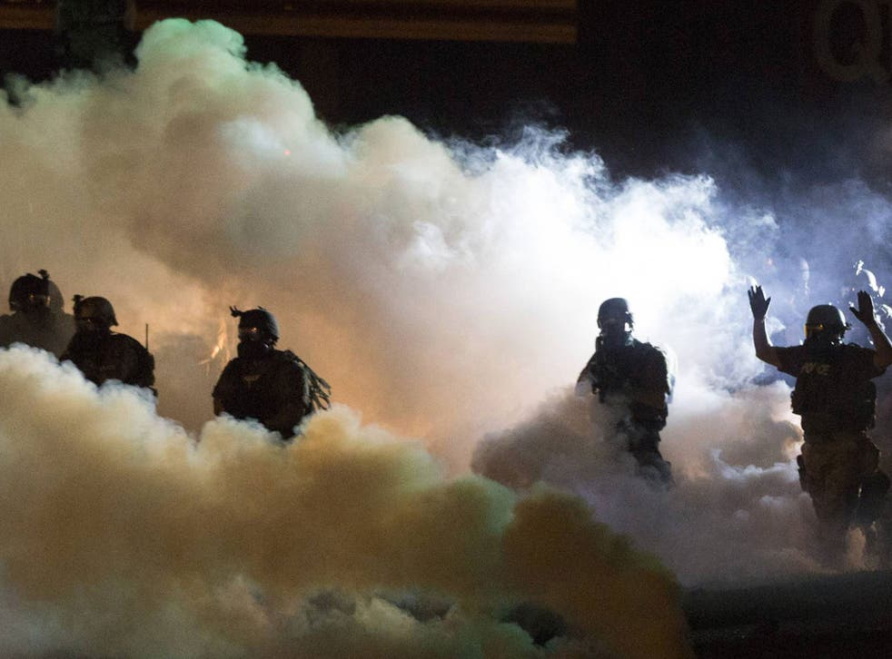 Riot police clear a street with smoke bombs while clashing with demonstrators in Ferguson, Missouri. State Senator Claire McCaskill has called for the 'demilitarisation' of the police response
