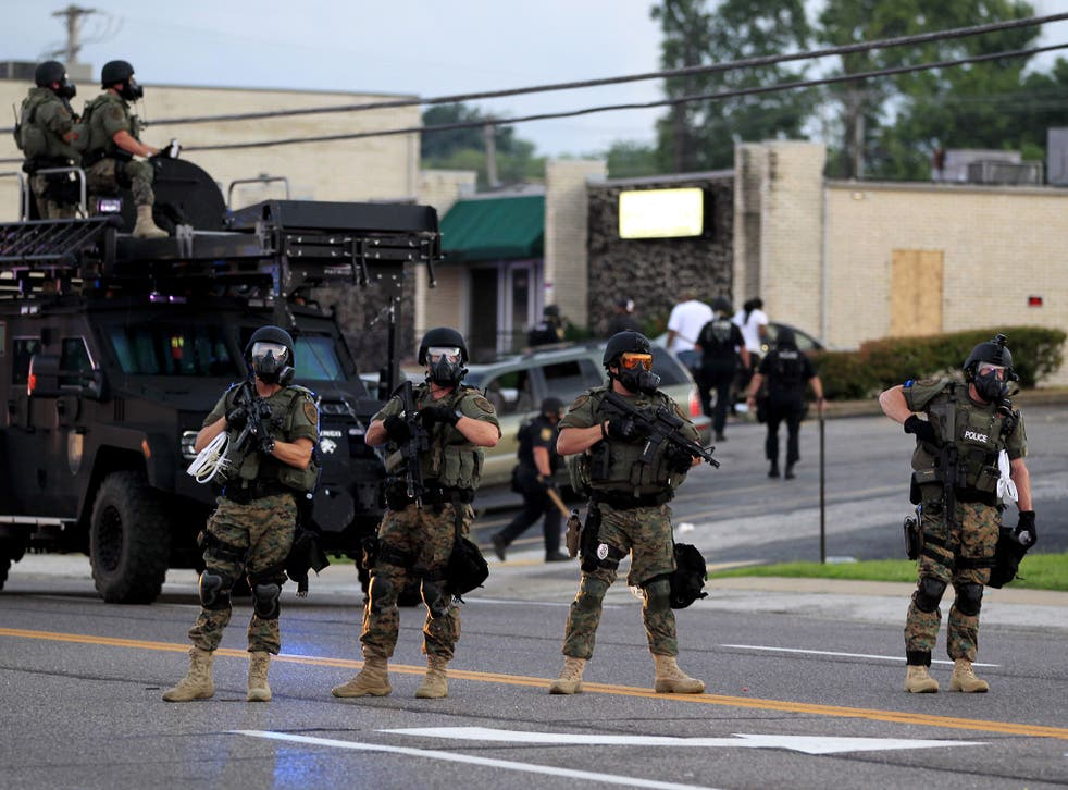 Police wearing riot gear try to disperse a crowd in Ferguson, Missouri