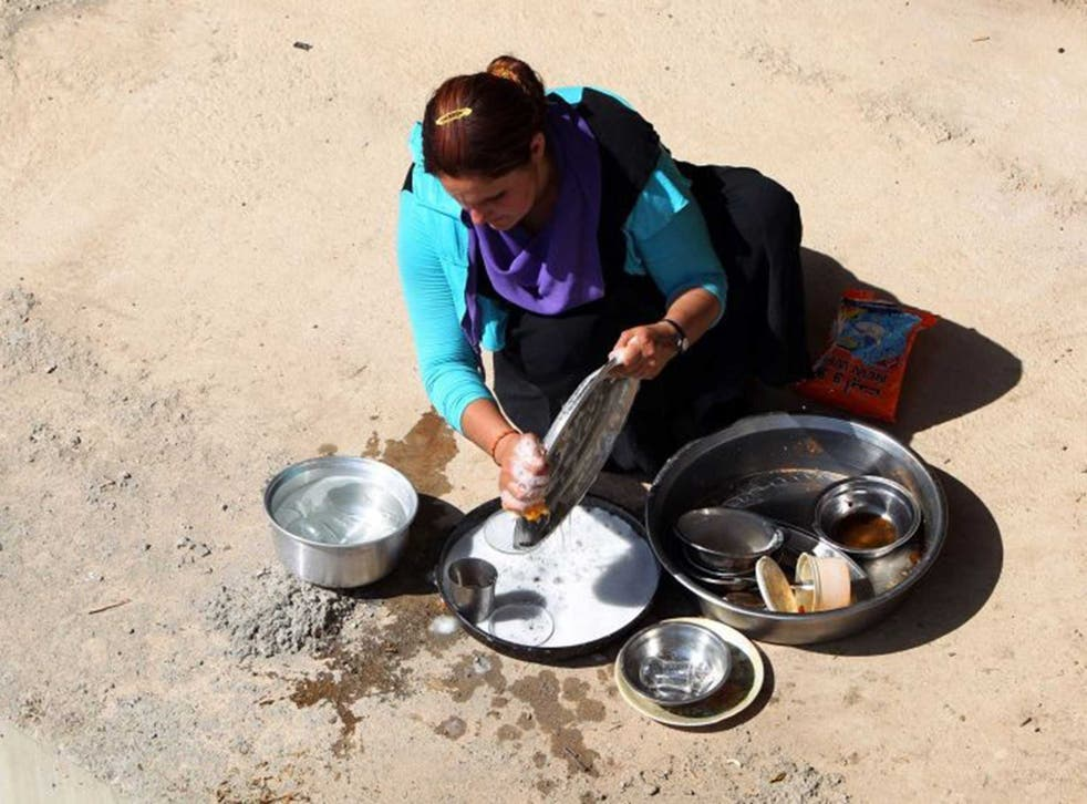 An Iraqi Yazidi woman, who fled her home when Islamic State militants attacked the town of Sinjar, cleans dishes