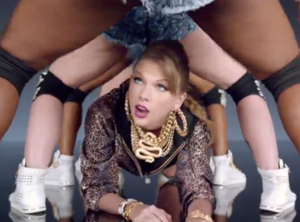 Taylor Swift crawls through the legs of twerking dancers in her 'Shake It Off' music video