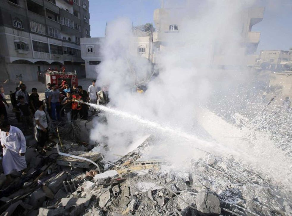 Palestinians help to put out a fire from the rubble of a house, which witnesses said was destroyed in an Israeli air strike, in Rafah