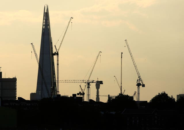 Construction cranes in front of The Shard in London